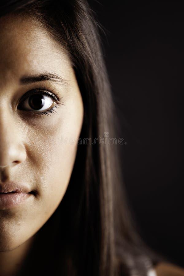 Demi de visage de fille féminine d'adolescent sur le noir images stock