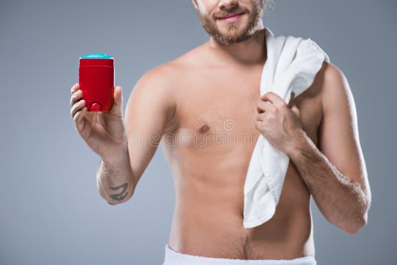 Demi homme nu de sourire tenant la serviette de bain au-dessus de l'épaule dans un main et stick déodorant dans des autres, photographie stock