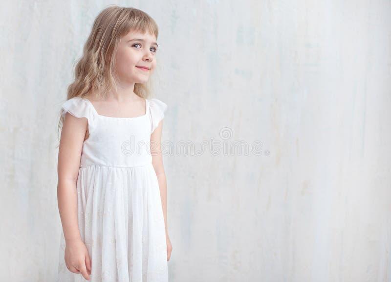 Demi-longueur de la fille assez petite dans la robe blanche au-dessus du fond image stock