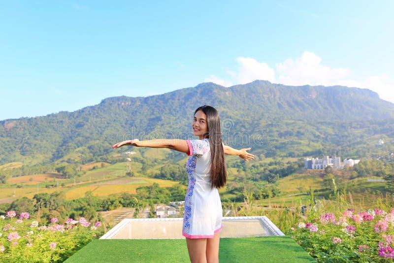 Demi-longueur du jeune sentiment asiatique de femme libre avec des bras grands ouverts à de beaux arbres et montagnes sur le ciel photos stock
