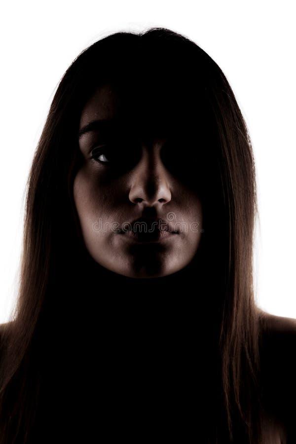 Demi silhouette d'une fille de brune regardant l'appareil-photo images libres de droits