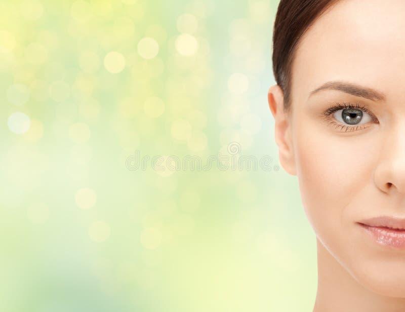 Demi visage de belle jeune femme au-dessus de vert photo stock