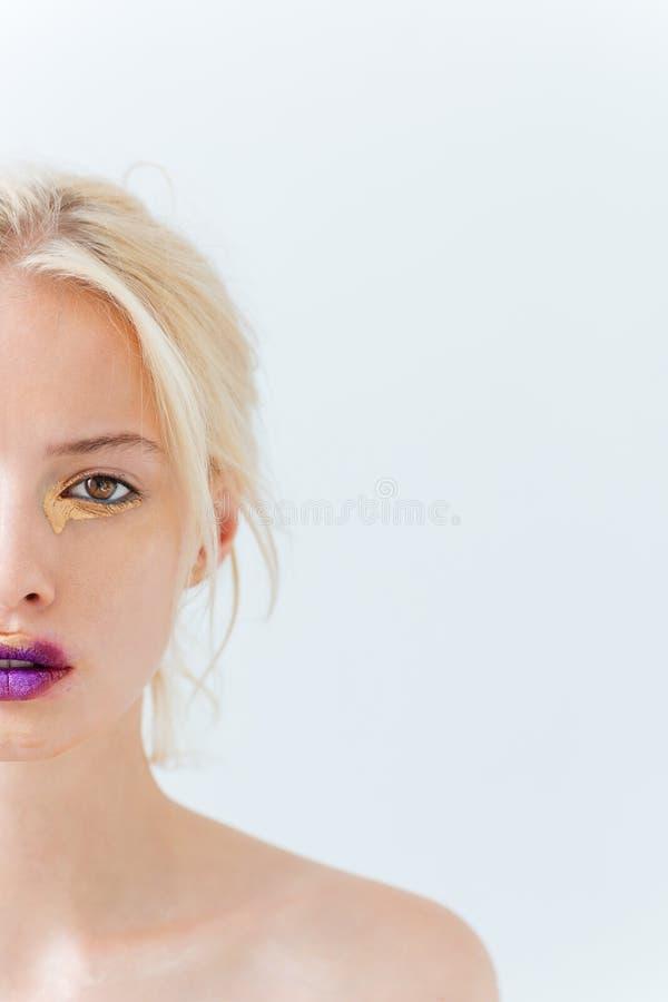 Demi visage de belle jeune femme avec le maquillage élégant pourpre photos stock