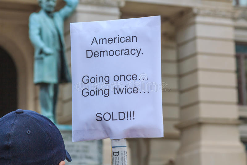 Democracy Bought and Sold. Protester holding a sign declaring that American democracy has been sold to the highest bidder with the most cash stock image