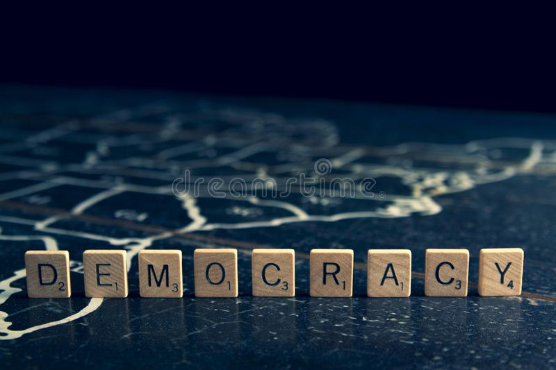 Democracy spelled with Scrabble tiles on map of United States stock photo
