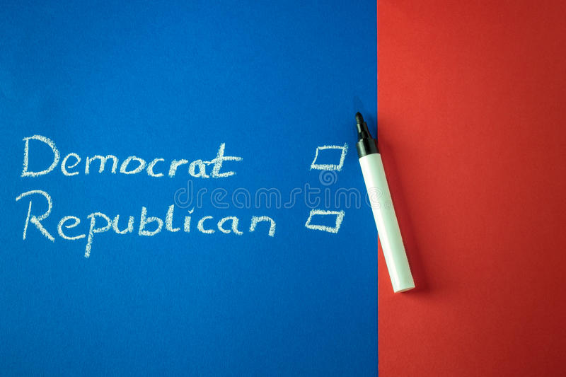 Democrat and Republican written with chalk. Democrat and Republican and checkboxes written with chalk on red and blue background. Copy space royalty free stock images