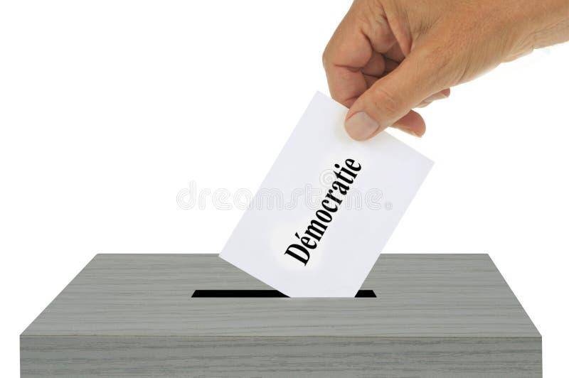 Democratie in het Frans op een stemming wordt geschreven die in de stembus die wordt gezet stock illustratie