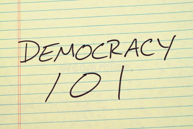 Democrazia 101 su un blocco note giallo fotografia stock