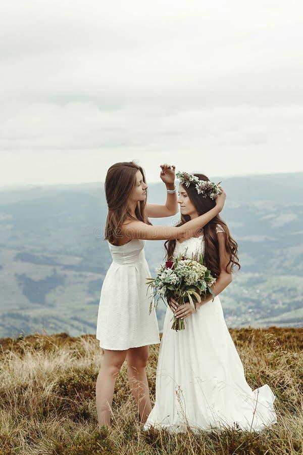 Demoiselle d'honneur élégante aidant la jeune mariée magnifique préparant, weddin de boho photographie stock libre de droits