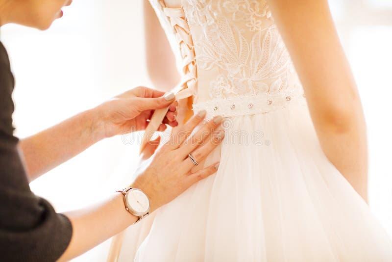 Demoiselle d'honneur aidant la jeune mariée à mettre sa robe de mariage dessus image stock