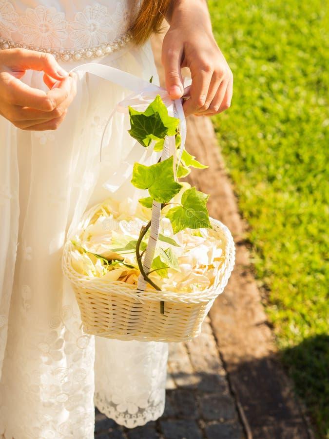 Demoiselle d'honneur dans la robe blanche avec le panier des pétales photos stock