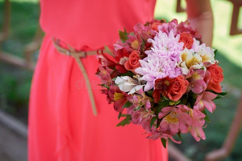 Demoiselles d'honneur dans une robe rouge avec le bouquet de mariage image libre de droits