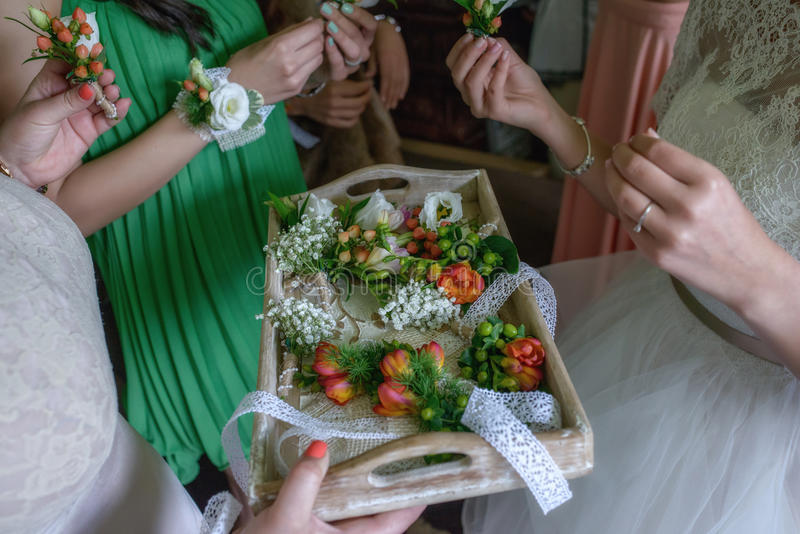 Demoiselles d'honneur sélectionnant des freesias et des boutonnieres de baies pour les invités de mariage photo stock
