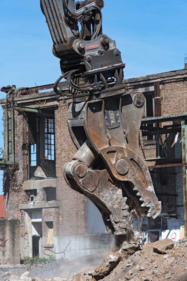 A demolição luta de uma máquina escavadora em um canteiro de obras durante imagens de stock royalty free