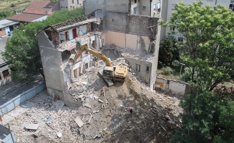 Demolición constructiva por el excavador de la oruga foto de archivo