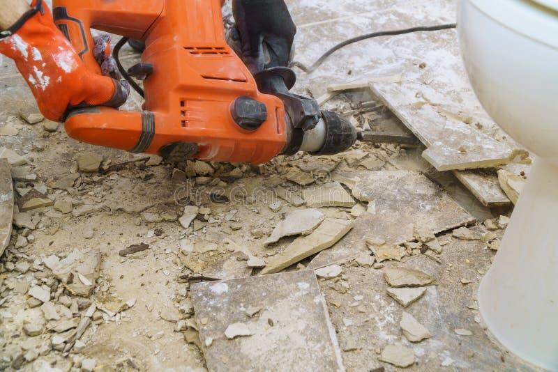 Demolición de tejas viejas con el martillo perforador Renovación del piso viejo imagenes de archivo