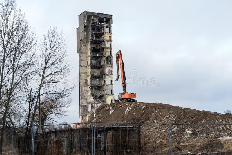 Demolición del edificio con el excavador hidráulico imagenes de archivo