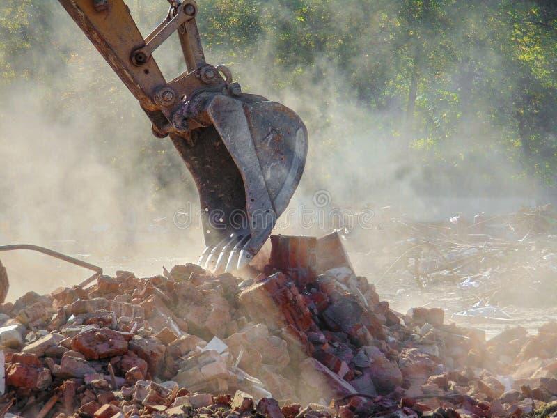 Demolición un edificio de ladrillo con un excavador del cubo foto de archivo libre de regalías