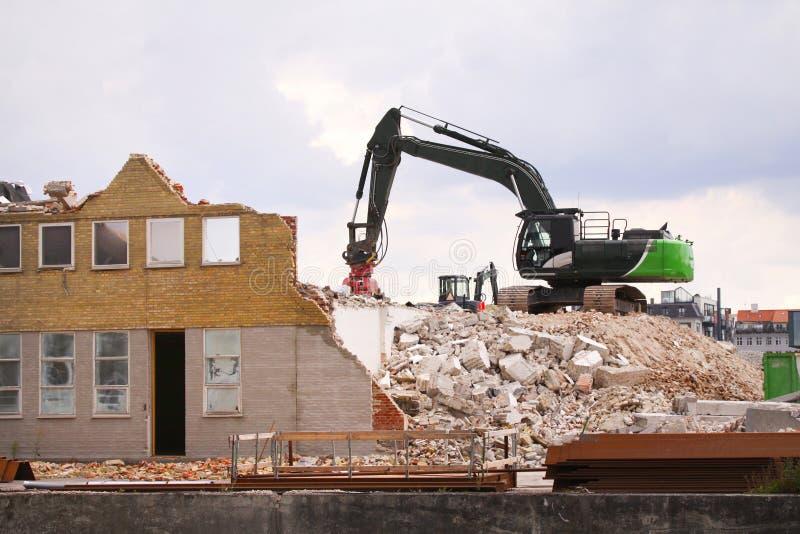 Demolierung des Gebäudes mit Gleiskettenfahrzeug an der Baustelle stockbilder