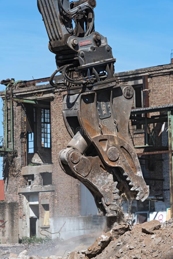 Demolierung halten sich von einem Bagger auf einer Baustelle während fest lizenzfreie stockbilder