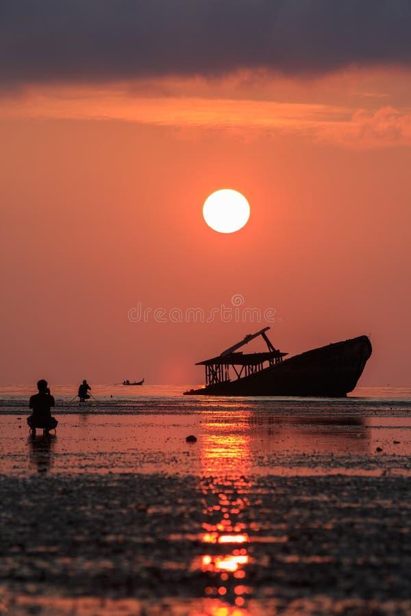 Demolisca la barca, il cielo in aumento del sole ed il fotografo a phuket Tailandia fotografie stock