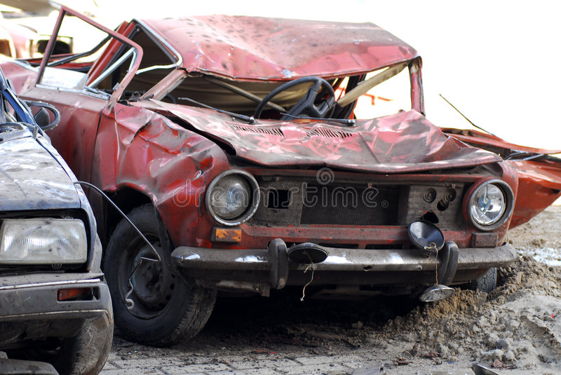 Demolished cars in junkyard. A view of two demolished cars in a junkyard stock images