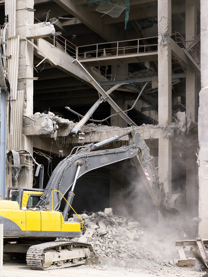 Demolishing. A bulldozer demolishing a old factory royalty free stock photos