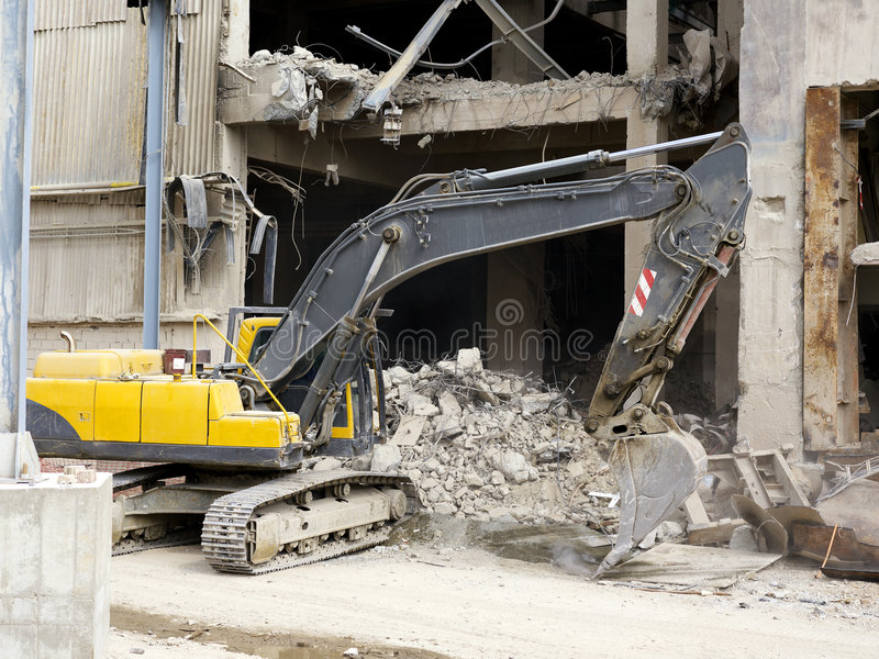 Demolishing. A bulldozer demolishing a old factory stock image