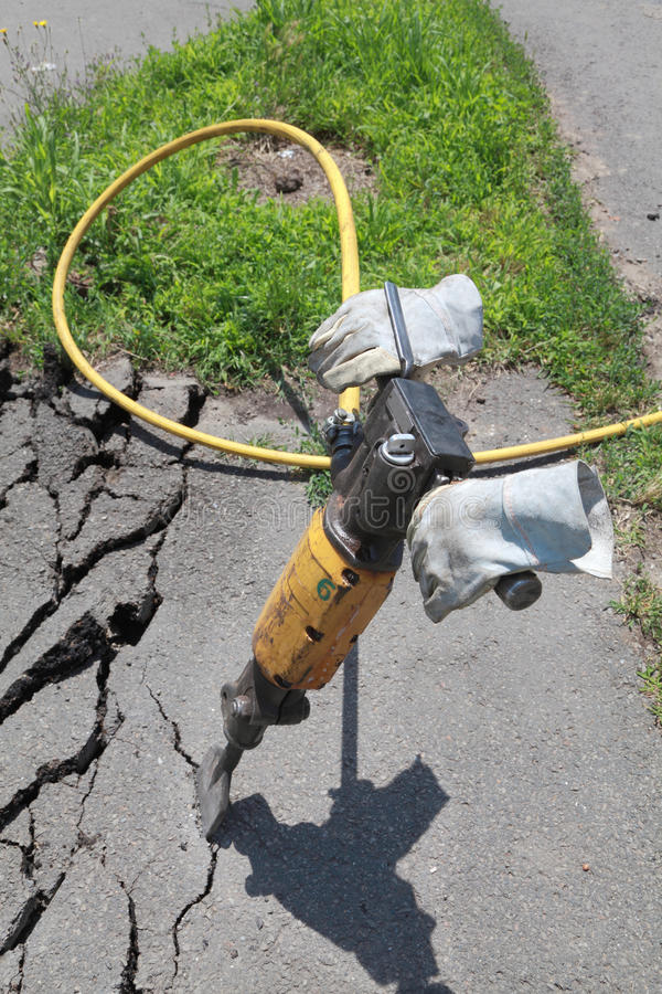 Demolishing asphalt. Asphalt demolishing with pneumatic jackhammer, equipment only stock image
