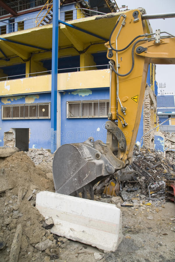 Demolition. An enormous machine in the demolition of a football stadium stock photography