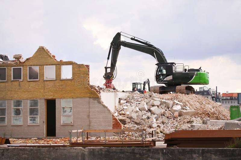 Demolition of building with caterpillar at construction site. Stock image stock images