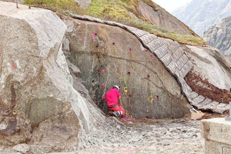 Demolition expert prepares charges for rock blasting. Near Lake Grimsel Dam Grimselsee - Upper Hasli Valley Oberhasli, canton Bern, Switzerland royalty free stock photos