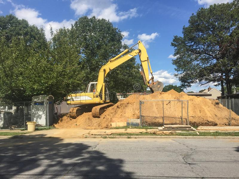 Demolizione della casa suburbana con il bulldozer sul mucchio della sporcizia fotografia stock libera da diritti