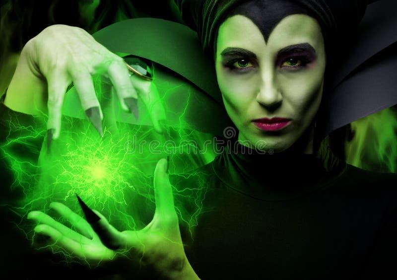 Demoníaco maléfico - protagonizando mujer impresionante que sostiene una bola mágica imagenes de archivo