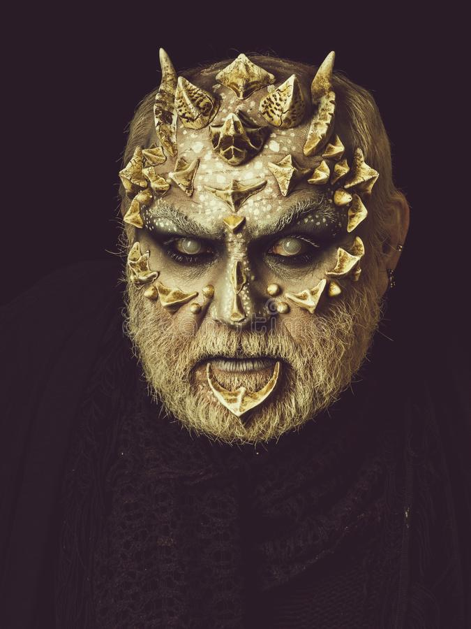 Demon baring teeth on black background. Monster with thorns and horns. Evil face with dragon skin and grey beard. Man angry with blind eyes. Horror and fantasy royalty free stock image