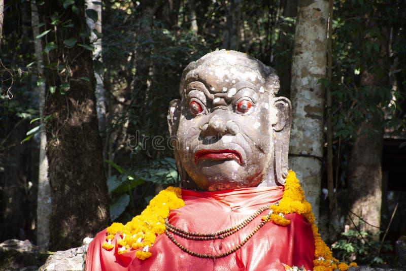 Demon eller jätte- ängelstaty i skogöverkant av berget på Wat Phra That Doi Tung i Chiang Rai, Thailand royaltyfri bild