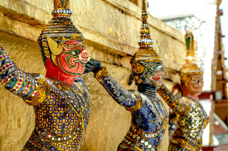 Demon Guardian/ Giant Statues stand around pagoda and hand to li. Ft the base of the golden pagoda of thailand at wat phra kaew royalty free stock images