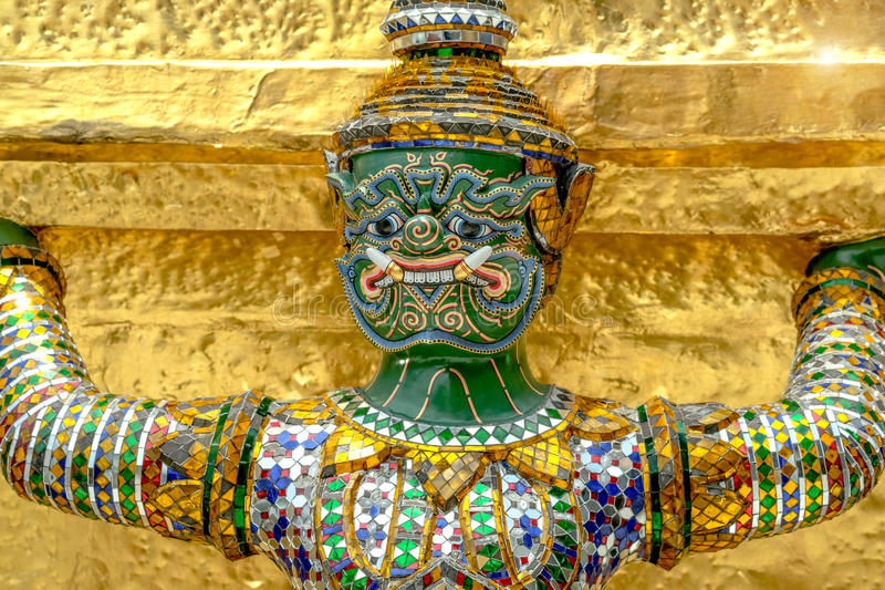 Demon Guardian/ Giant Statues stand around pagoda and hand to li. Ft the base of the golden pagoda of thailand at wat phra kaew stock photos