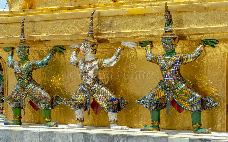 Demon Guardian/ Giant Statues stand around pagoda and hand to li. Ft the base of the golden pagoda of thailand at wat phra kaew stock image