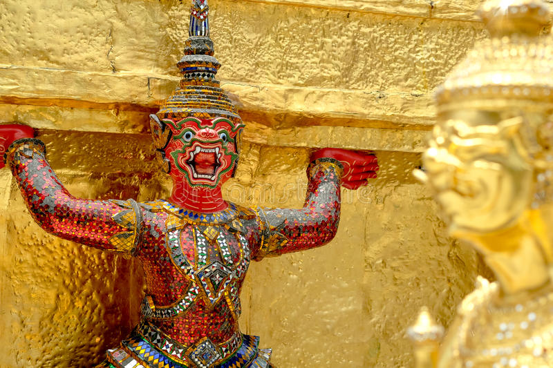 Demon Guardian/ Giant Statues stand around pagoda and hand to li. Ft the base of the golden pagoda of thailand at wat phra kaew stock photo