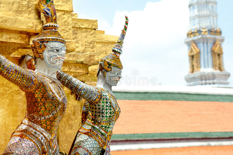 Demon Guardian/ Giant Statues stand around pagoda and hand to li. Ft the base of the golden pagoda of thailand at wat phra kaew royalty free stock photo