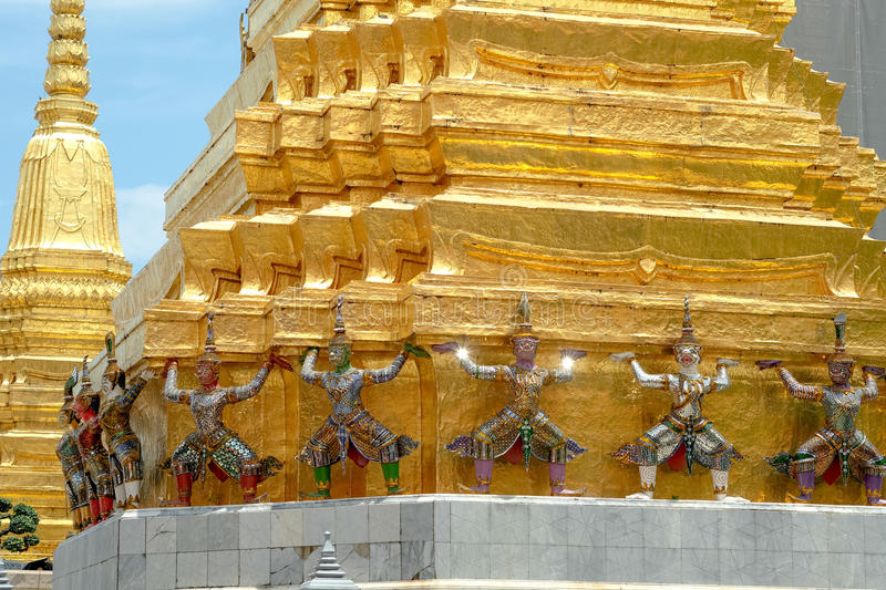 Demon Guardian/ Giant Statues stand around pagoda and hand to li. Ft the base of the golden pagoda of thailand at wat phra kaew royalty free stock photos