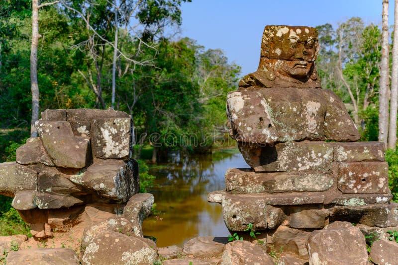 Demon som är stupad ifrån varandra på templet av Angkor Thom, Cambodja arkivfoton