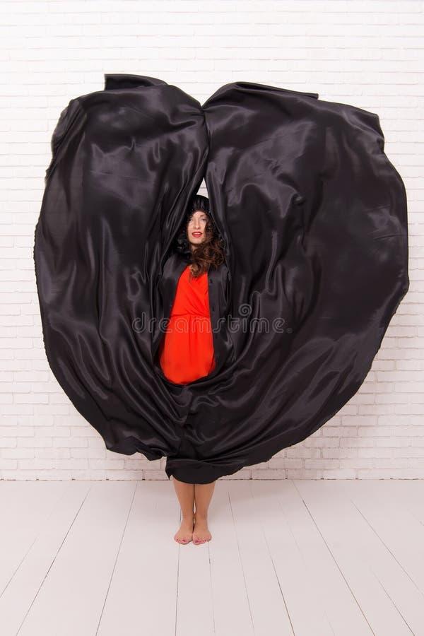 Demon van de vrouwen het verleidende vampier Meisje omvat met mantel duivelsconcept Halloween-maskerade De partij van Halloween V stock fotografie