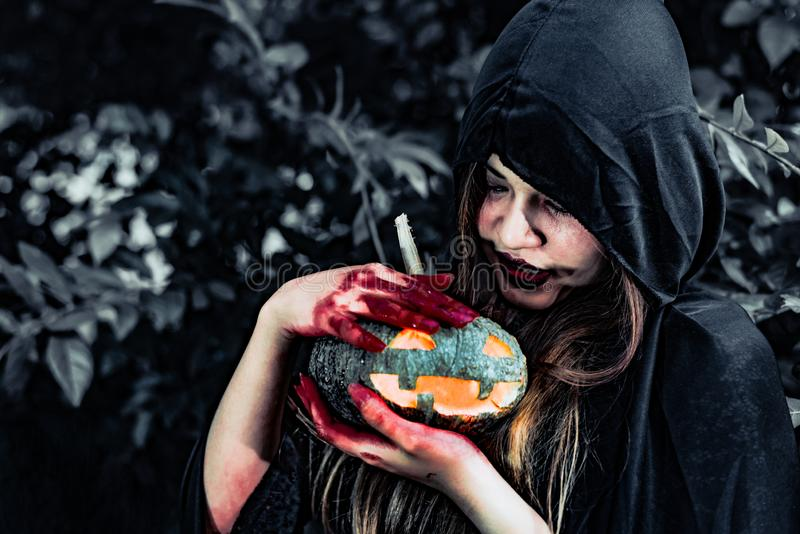 Demon witch take care of pumpkin in the mystery forest. Ghost and Horror concept. Halloween day theme. Red blood on witch hands royalty free stock images