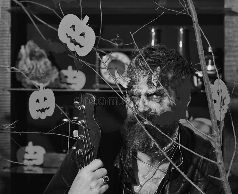 Demon z rogami i złą twarzą trzyma czarną gitarę elektryczną Obsługuje być ubranym strasznego makeup za Halloweenowymi baniami i  zdjęcie stock