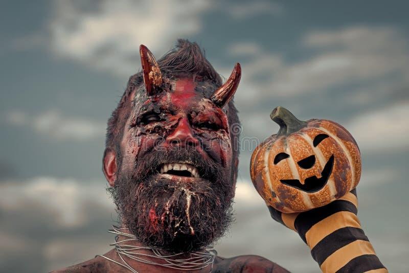 Demonio de Halloween que sonríe con los cuernos sangrientos en la cabeza fotos de archivo libres de regalías