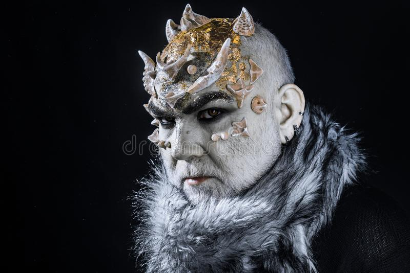 Demonio severo con la piel blanca pálida teñida con oro Nieve que controla y helada, dios de la criatura malvada del invierno Mon imagen de archivo