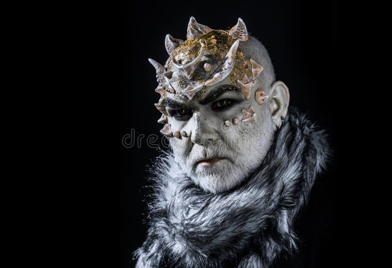 Demonisk varelse med taggar på huvudet som isoleras på svart bakgrund Konung av sfären av evig förkylning Man med uppdiktat royaltyfri foto