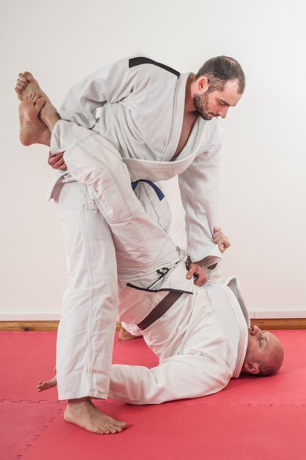 Demonstração brasileira do treinamento do jiu-jitsu no quimono tradicional imagens de stock
